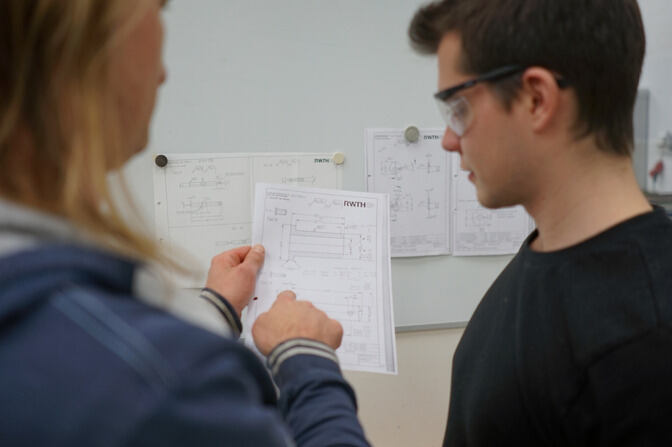 Two people are studying a construction plan